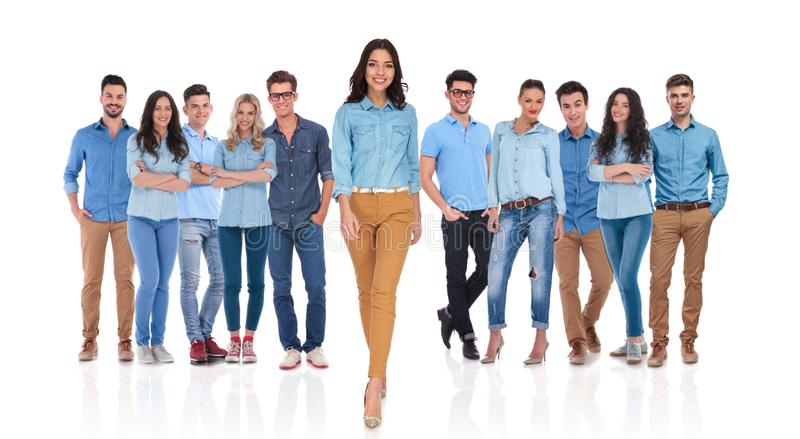Young casual woman walking forward in front of her group royalty free stock image