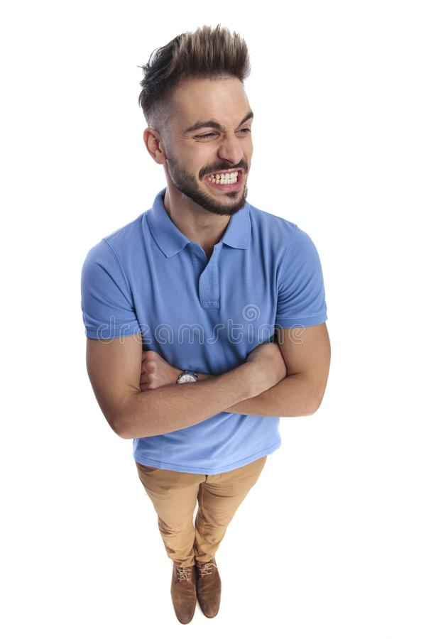 Young casually-dressed man wearing a light blue polo looking at a side. Maybe at something gross, holding his hands crossed royalty free stock photography