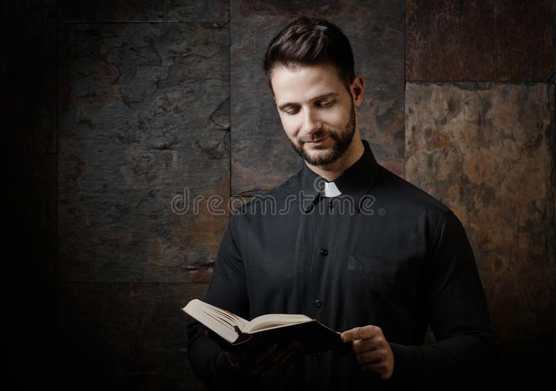 Young catholic priest reading from prayer book stock photo