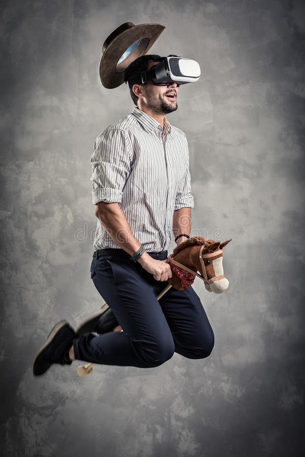 Young caucasian adult man enjoy experiencing immersive Virtual Reality cowboy game simulation.VR portrait concept with royalty free stock image