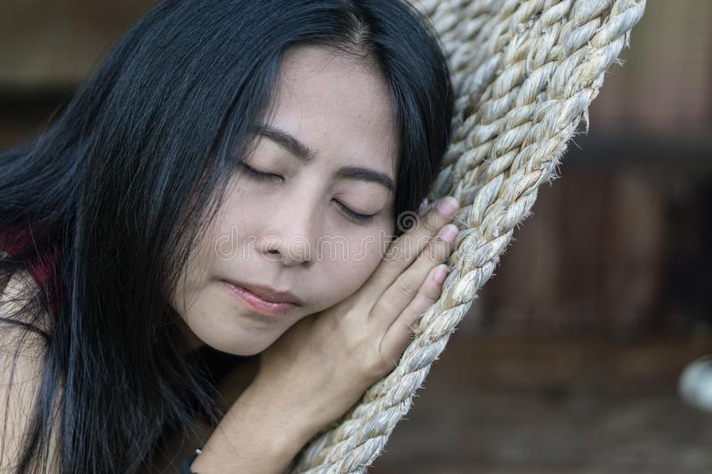 Young caucasian asian girl swinging in a hammock in a pleasant laziness of a weekend evening. She is smiling through her beard., holiday at riverside in royalty free stock photo