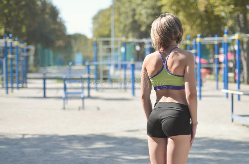 A young caucasian athlete girl in a bright green sportswear stands against the backdrop of a street sports playground for outdoor stock image