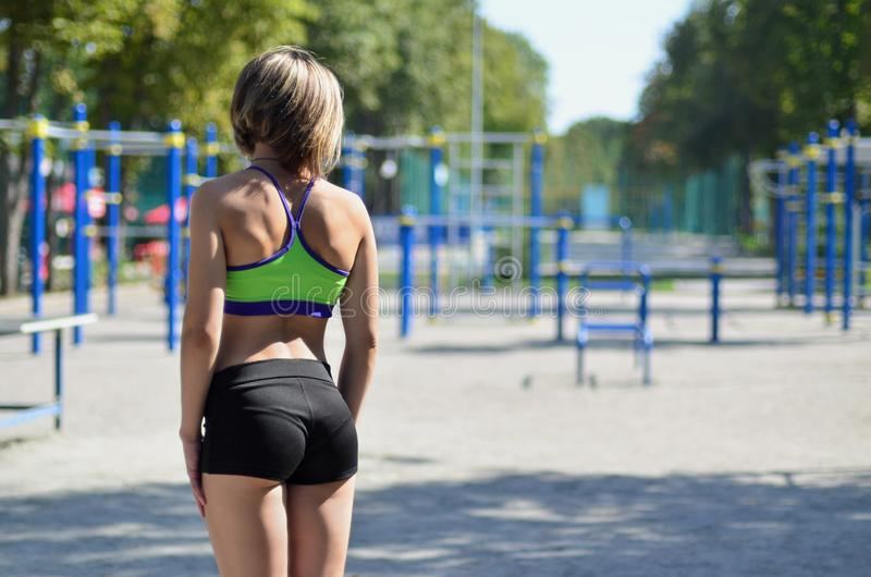 A young caucasian athlete girl in a bright green sportswear stands against the backdrop of a street sports playground royalty free stock photography