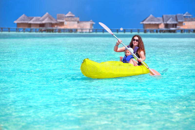 Young caucasian attractive woman with her little son kayaking on tropical island royalty free stock photos