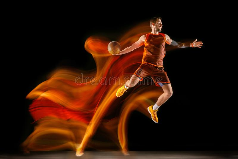 Young caucasian basketball player against dark background in mixed light royalty free stock photography
