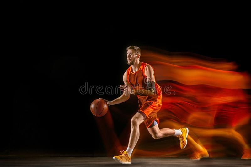 Young caucasian basketball player against dark background in mixed light stock photos