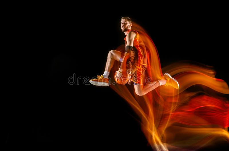 Young caucasian basketball player against dark background in mixed light royalty free stock image
