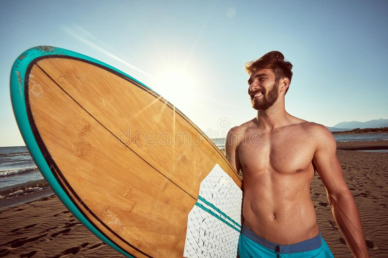 Young caucasian beardy male walking on the sunny beach, holding surfboard, smiling. ultraviolet radiation concept royalty free stock photo