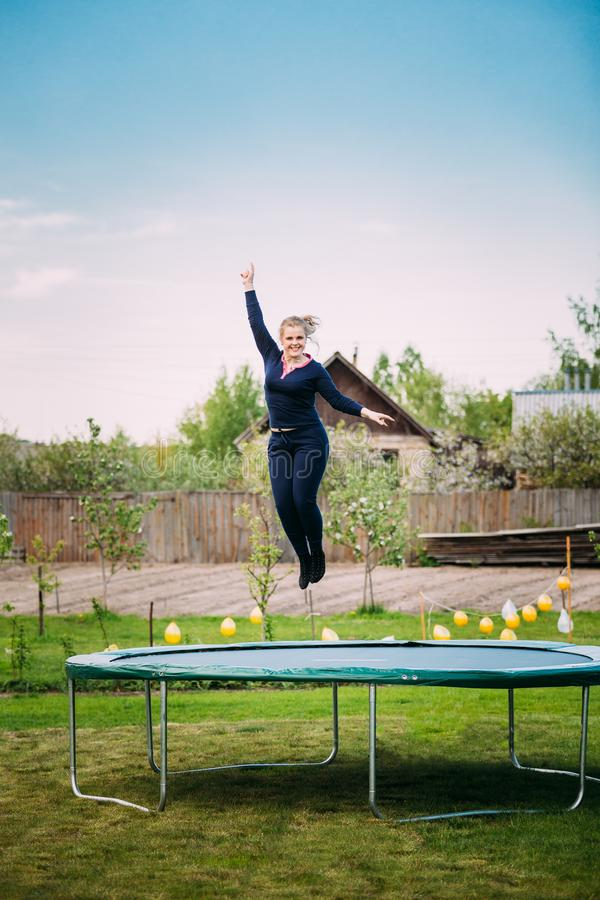Young Caucasian Beautiful Plus Size Woman Girl Jumping On Trampo. Young White Caucasian Beautiful Plus Size Woman Girl Jumping On Trampoline In Summer Cloudy Day royalty free stock images