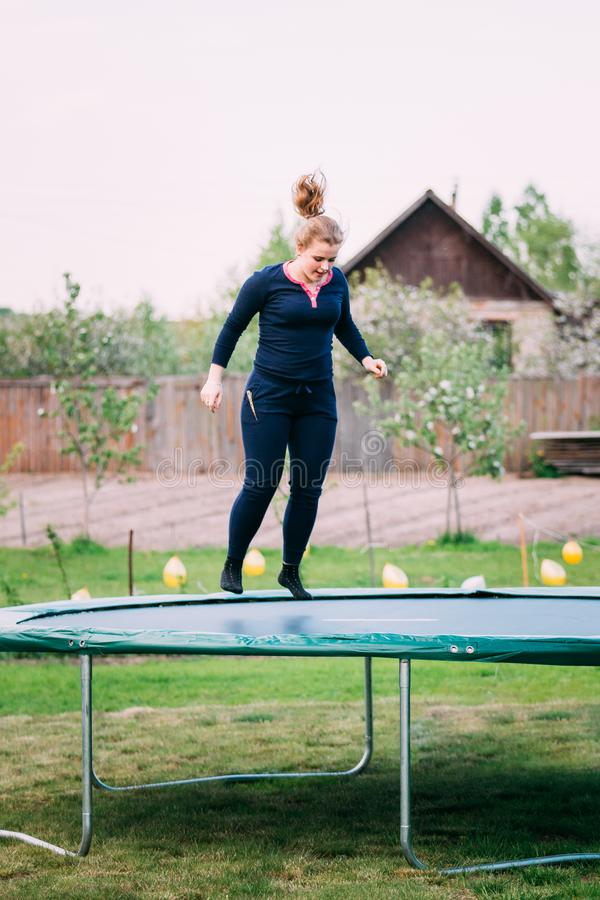 Young Caucasian Beautiful Plus Size Woman Girl Jumping On Trampoline. Young White Caucasian Beautiful Plus Size Woman Girl Jumping On Trampoline In Summer Cloudy stock images