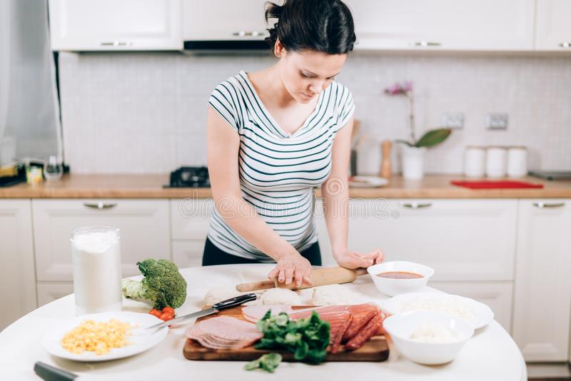 Young caucasian, beautiful pregnant woman preparing dough for pizza stock photography