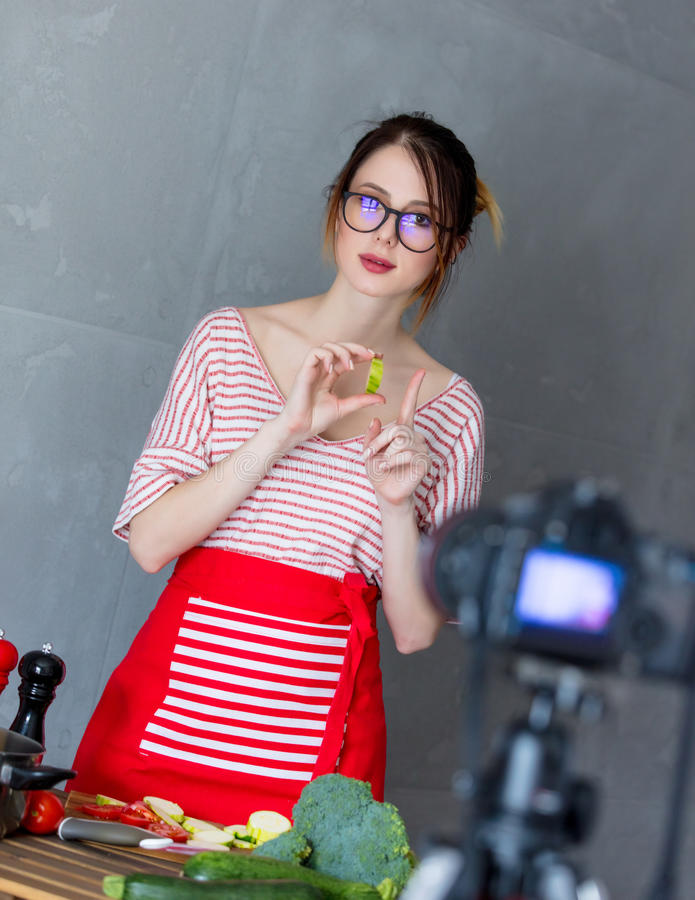 Young caucasian blogger woman cooking Vegan food. At camera for Video-sharing website. Home location at kitchen royalty free stock photo