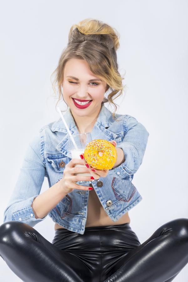 Young Caucasian Blond Girl Offering Doughnut in Hand Pointing Towards stock photo