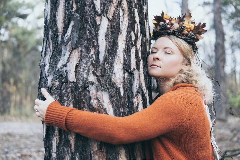 Young Caucasian blonde woman in the autumn wreath hugging a pine tree with her eyes closed royalty free stock photography