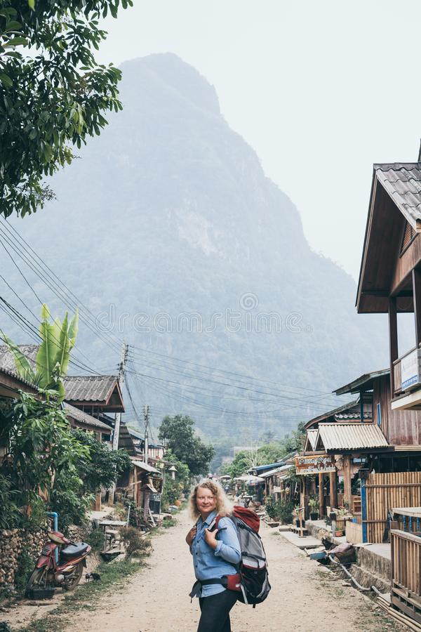 Young Caucasian blonde woman with backpack standing on the central street of Muang Ngoi village, Laos. Vertical orientation, laotian, southeast, discover stock photo