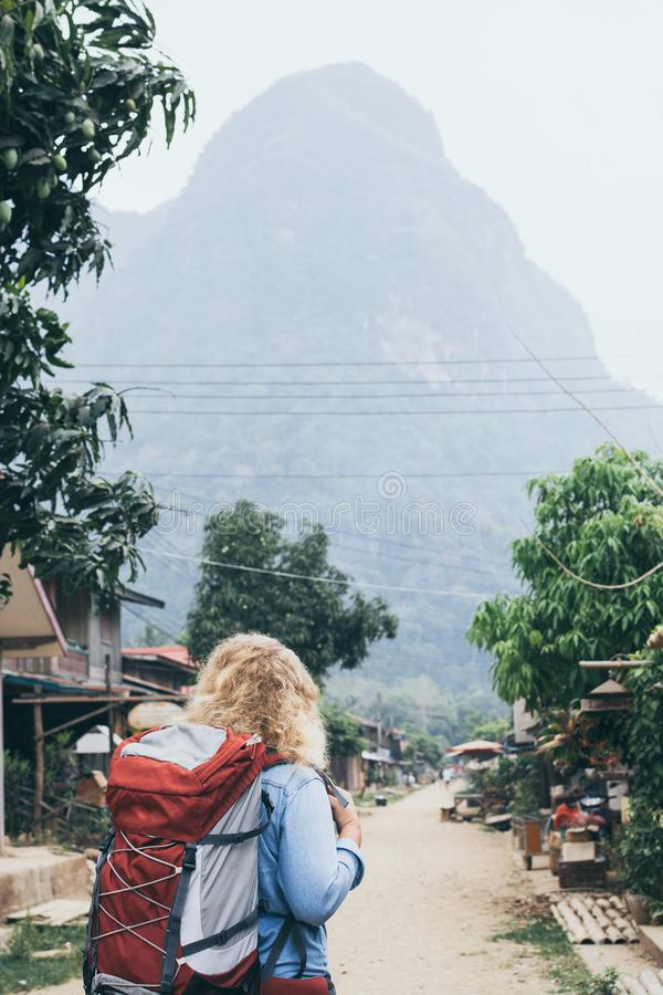 Young Caucasian blonde woman with backpack standing on the central street of Muang Ngoi village, Laos. Vertical orientation, laotian, southeast, discover royalty free stock photo