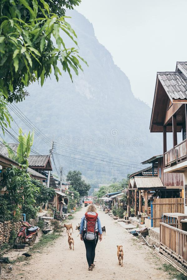 Young Caucasian blonde woman with backpack walking on the central street of Muang Ngoi village, Laos. Accompanied by stray dogs. Vertical orientation, laotian stock image