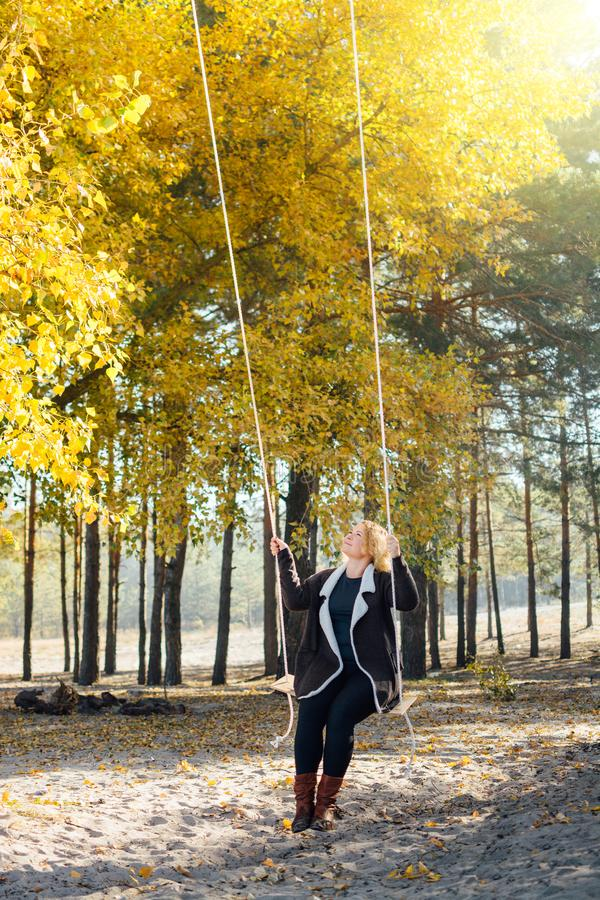 Young caucasian blonde woman in brown cardigan riding a swing in yellow autumn forest. Vertical orientation.  royalty free stock image