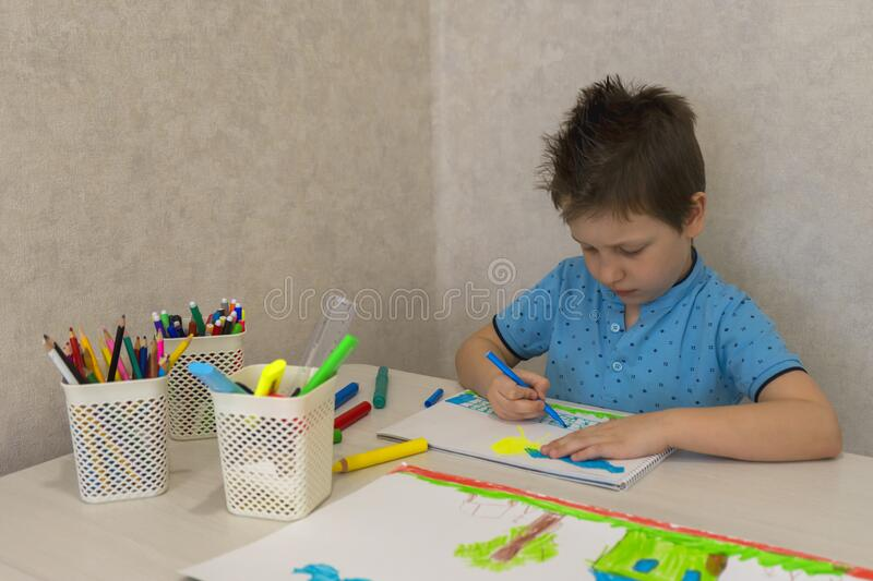A young Caucasian boy draws with pencils on white paper.  stock photo
