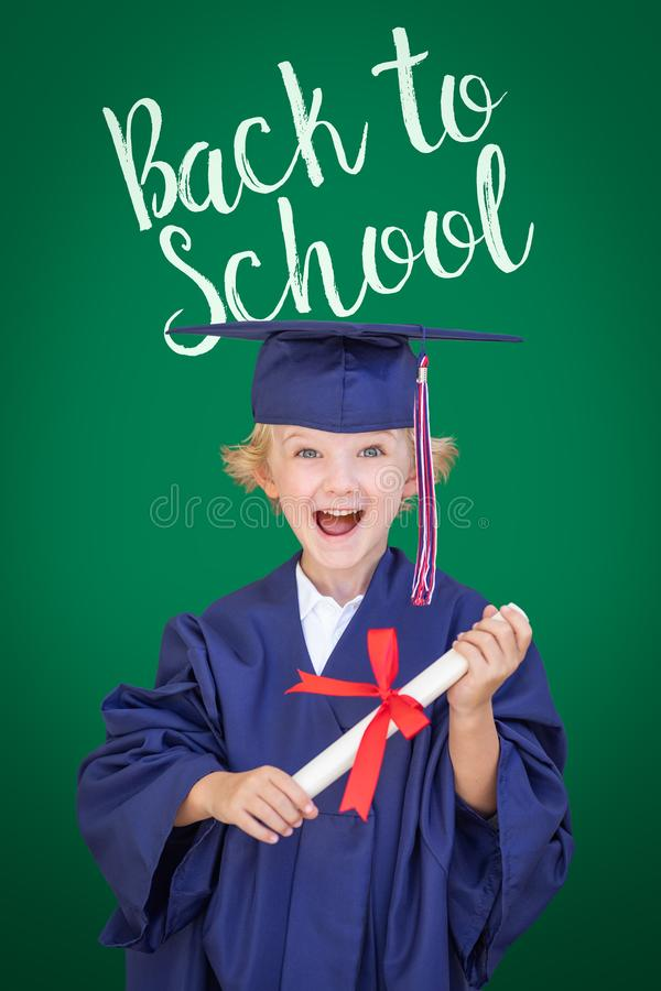 Young Caucasian Boy In Graduation Cap and Gown Against Green Chalkboard Background With Back To School royalty free stock photos