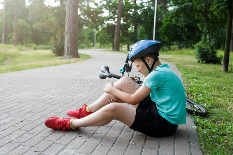 Young caucasian boy in helmet and green t shirt got accident and sits on the ground after falling from the bicycle and feels pain royalty free stock photos