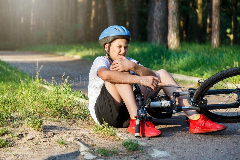 Young caucasian boy in helmet and white t shirt got accident and sits on the ground after falling from the bicycle and feels pain stock photo