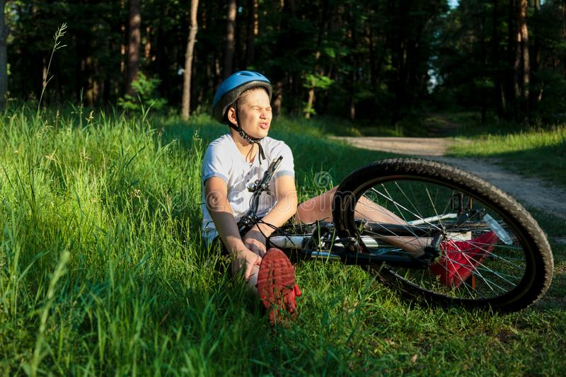 Young caucasian boy in helmet and white t shirt got accident and sits on the ground after falling from the bicycle and feels pain royalty free stock photo
