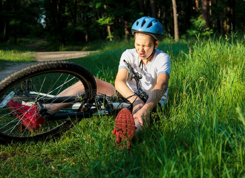 Young caucasian boy in helmet and white t shirt got accident and sits on the ground after falling from the bicycle and feels pain royalty free stock photography