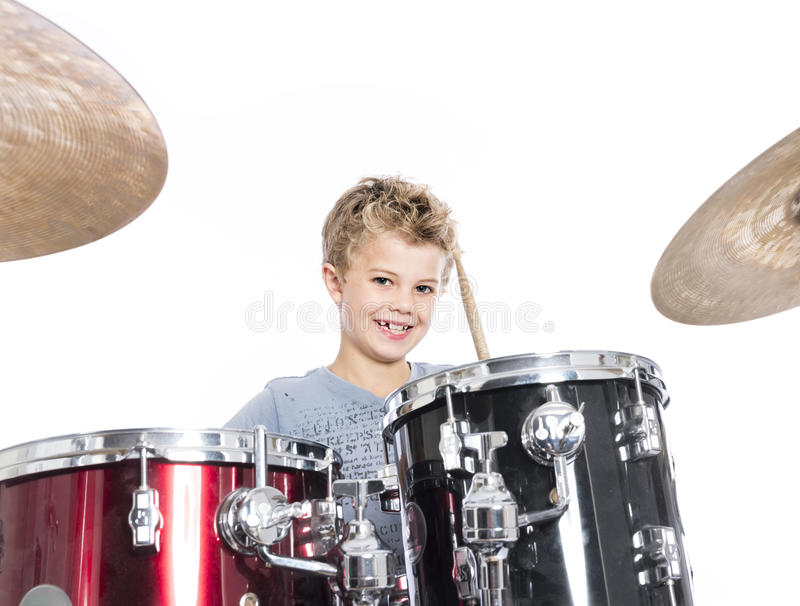 Young caucasian boy plays drums in studio against white background. Young blond caucasian boy plays drums in studio against white background royalty free stock image