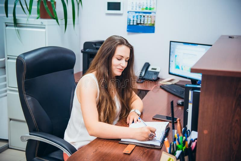 Young caucasian business lady sitting on her workplace in office. Female entrepreneurship. Portrait of skilled manager satisfied royalty free stock photos
