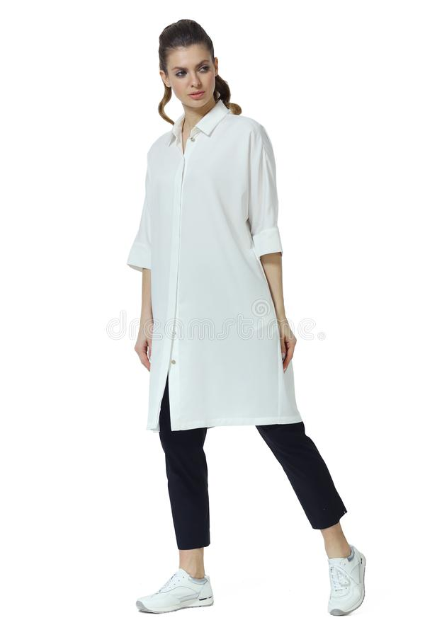 Young caucasian business woman executive posing in white baggy shirt trousers stock image