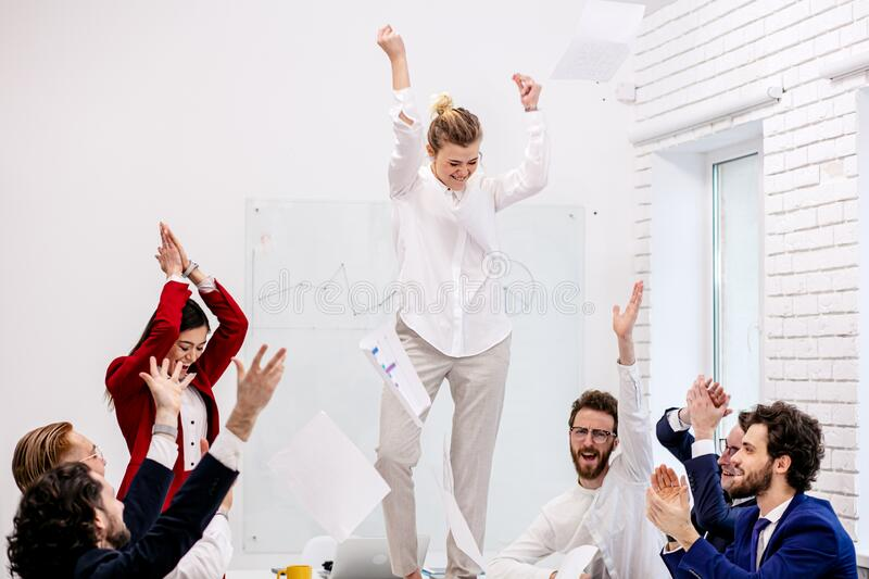 Young caucasian business woman dance on table in office royalty free stock photography
