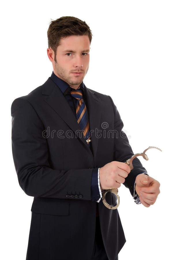 Young caucasian businessman, handcuffs. Young caucasian businessman who put handcuffs on hand . Studio shot. White background royalty free stock photo