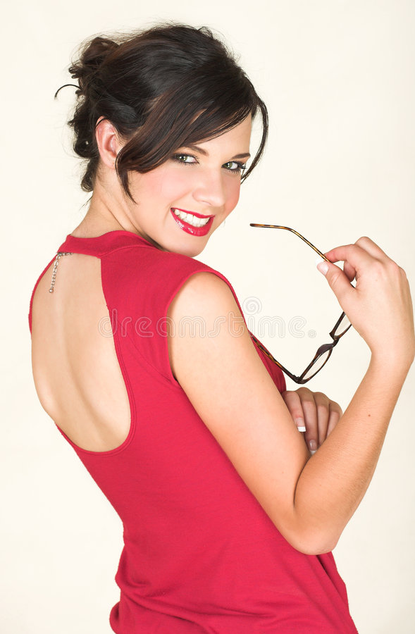Young caucasian businesswoman. Young adult brunette businesswoman with horn rimmed glasses and a red dress. She is Caucasian and wears bright red lipstick. White royalty free stock images