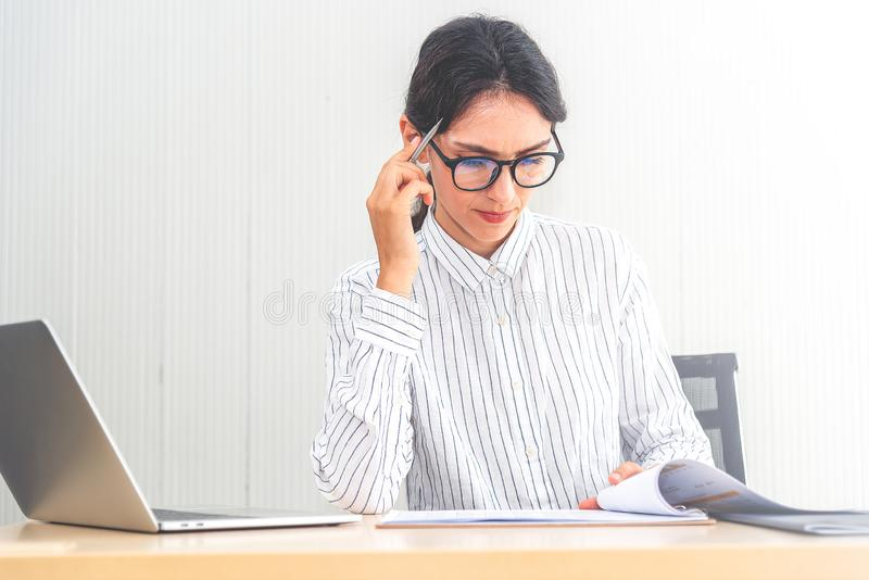 Young caucasian businesswoman working on laptop and thinking  in modern office. Smart businesswomen seriously working on her work stock photography