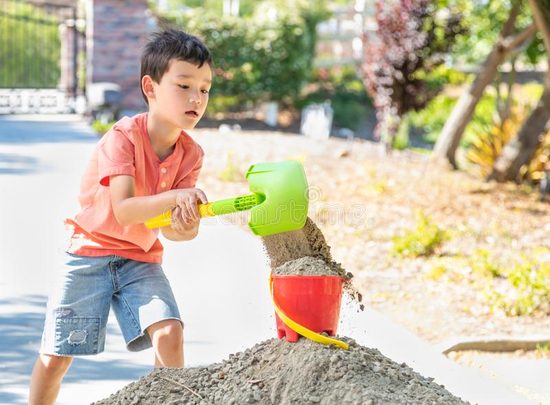Young Caucasian Chinese Boy Playing with Shovel and Bucket royalty free stock photos