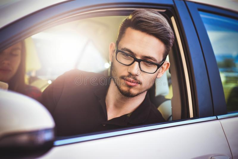 Young caucasian couple in car having fun on road trip and use a smartphone. royalty free stock photos