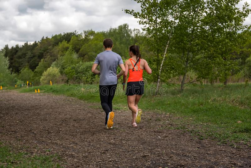 A couple - young man and woman jogging in nature - rear view stock photos