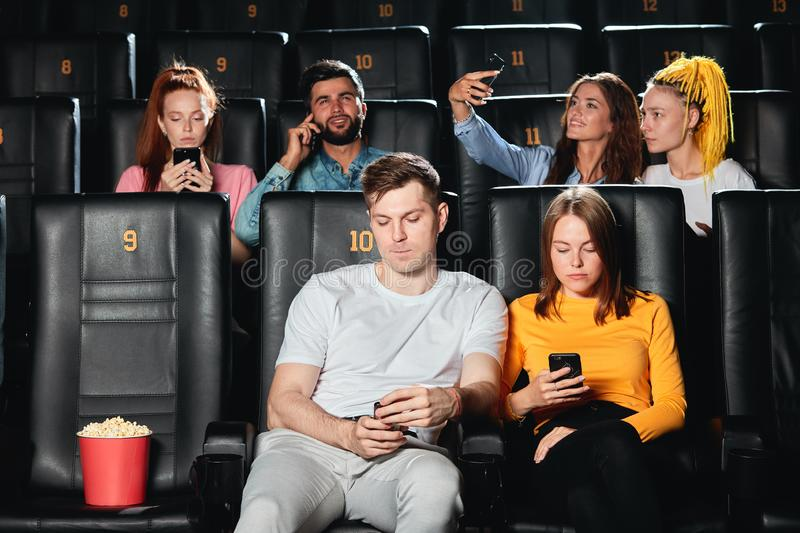 Young caucasian couple feeling bored at cinema session. royalty free stock images