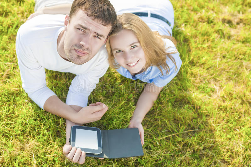 Young Caucasian Couple in love Outdoors Lying on Grass and Having Great Time Together. Reading Ebook Together stock photos