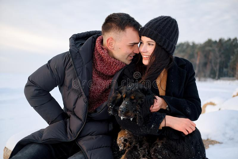 Young caucasian couple in love sitting on stone with dog on winter beach, embracing, enjoy the romantic moment, feeling intimacy royalty free stock photo