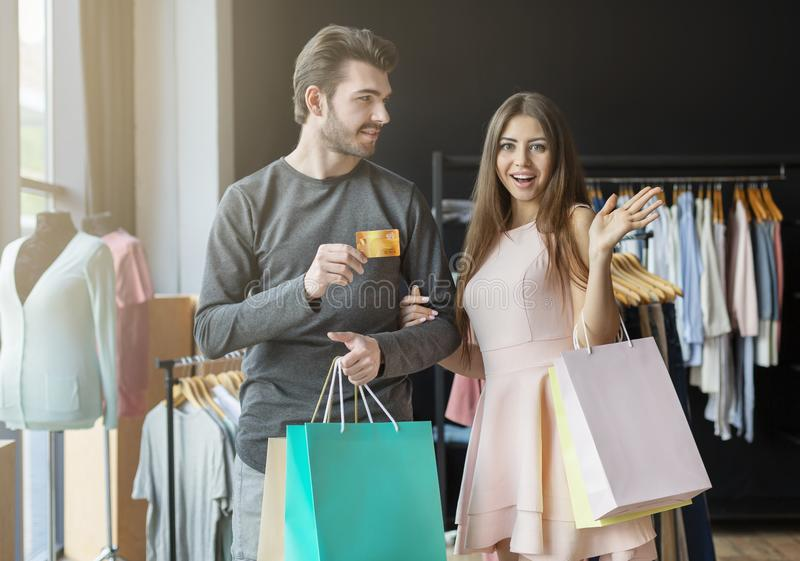 Young caucasian couple with shopping bags and credit card royalty free stock photography