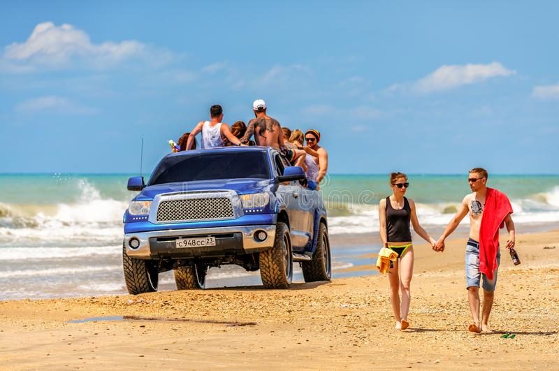 Young Caucasian couple walk on the sand of sunny Black Sea Blaga beach resort holding hands at summer with car full of partying royalty free stock photos