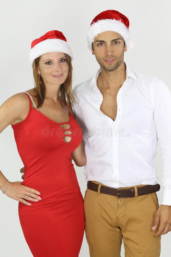 Young caucasian couple wearing a Santa hat. Over a white background stock photography