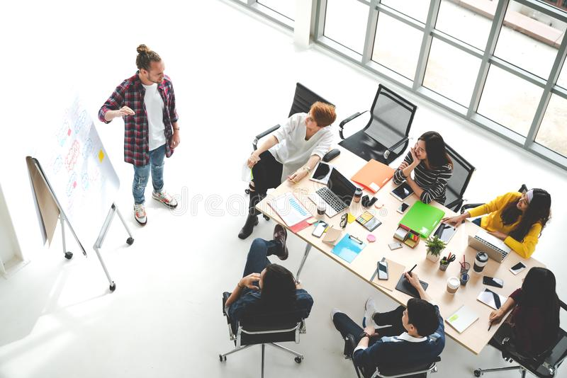 Young caucasian creative man standing and making presentation at modern office happy talking and brainstorming with team. royalty free stock photography