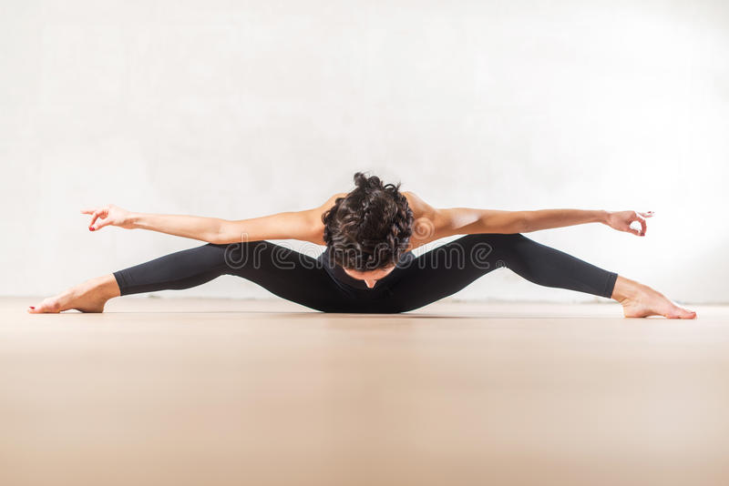 Young Caucasian dancer doing seated wide leg forward bend exercise stretching spine and legs stock image