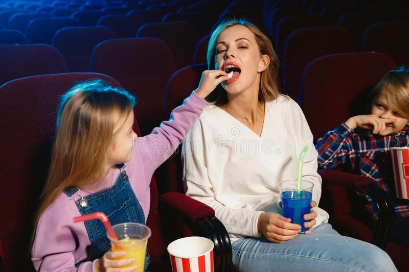 Young caucasian family watching a film at a movie theater royalty free stock photo