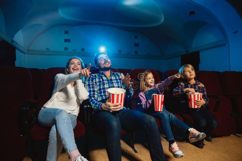 Young caucasian family watching a film at a movie theater stock photography