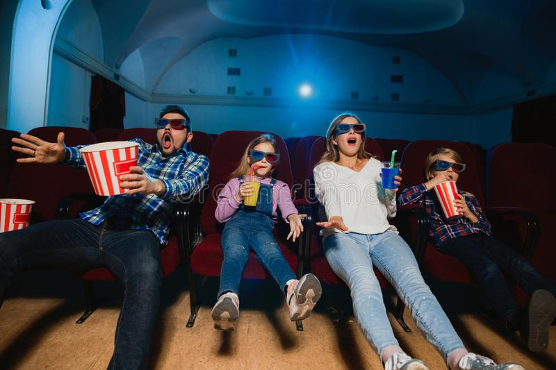 Young caucasian family watching a film at a movie theater stock photos