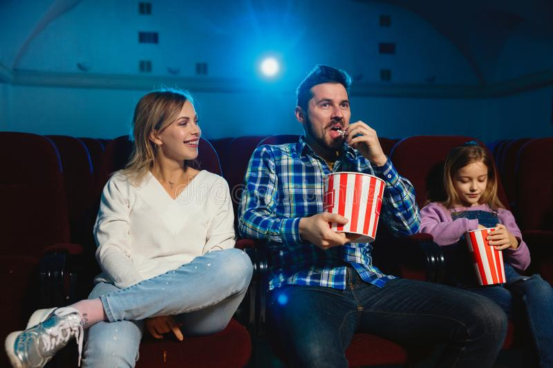 Young caucasian family watching a film at a movie theater stock images